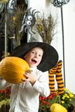 Halloween Kid with orange pumpkin in witch hat. Halloween child with happy face. Small boy in spider web hat at striped socks. Holiday and celebration. Party stock images