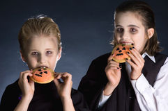 Halloween kids. Boys dressed up for Halloween party eating Halloween cookies Stock Photography