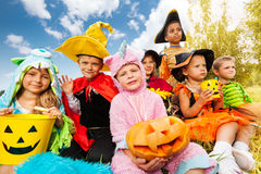 Halloween kids in beautiful costumes sitting. Together on the grass of the field and look happily royalty free stock photos
