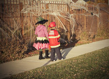 Halloween kids Trick or Treat. Two kids in Halloween costumes walking in the neighborhood going door to door trick or treating Royalty Free Stock Photography