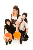 Halloween Kids Want Candy. Adorable trick or treaters in halloween costumes, begging for candy.  Full body isolated on white Royalty Free Stock Photos