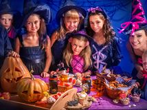 Halloween kids with woman holding carved pumpkin . Royalty Free Stock Image
