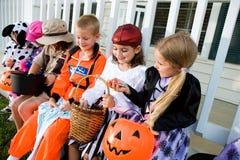 Halloween: Kinder, die Halloween-Süßigkeit vergleichen Stockbilder