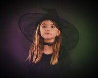 Halloween-Kinderhexe auf schwarzem Hintergrund stockfotografie