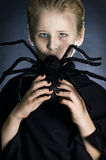 Halloween kiss. Boy dressed up as a vampire for halloween party kissing/sucking giant spider Royalty Free Stock Photography
