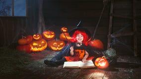Halloween kleine Hexe beschwört mit Buch von Bannen, Magie Stockfotos