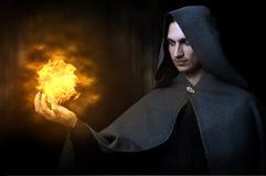 Halloween-Konzept. Männlicher Zauberer mit Feuerkugel Stockbild