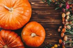 Halloween-Konzept mit frischen Kürbisen und Blumen auf dem Holztisch Süßes sonst gibt's Saures Ansicht von oben Lizenzfreie Stockfotos