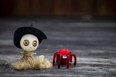 Halloween-Konzepthintergrund der hölzernen Hexenpuppe mit roter Wollspinne Lizenzfreie Stockfotografie