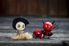 Halloween-Konzepthintergrund der Puppe der hölzernen Hexe und des roten Teufels mit roter Wollspinne Stockbild