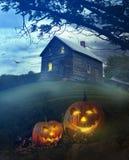 Halloween-Kürbise vor gespenstischem Haus Stockfotografie