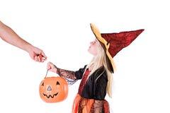 Halloween : L'adulte donne la sucrerie à la sorcière d'enfant Photos libres de droits