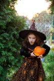 Halloween La ragazza di 7-8 anni rappresenta il mago arrabbiato Immagine Stock