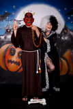 Halloween lady Cruella de vil. Young woman, Halloween lady impersonating Cruella de Vil next to devil character. Studio, painted themed background Royalty Free Stock Photos