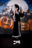 Halloween lady Cruella de vil. Young woman, Halloween lady impersonating Cruella de Vil. Studio, painted themed background Royalty Free Stock Image