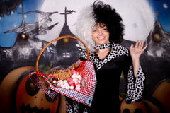 Halloween lady Cruella de vil. Young woman, Halloween lady impersonating Cruella de Vil. Studio, painted themed background Stock Photography