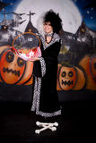 Halloween lady Cruella de vil. Young woman, Halloween lady impersonating Cruella de Vil. Studio, painted themed background Stock Photo