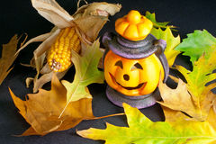 Halloween Lantern with Leafs and Corn. Happy Halloween pumpkin lantern with scary face Royalty Free Stock Image