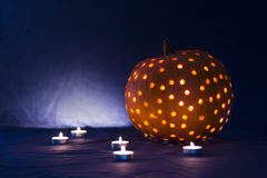 Halloween latern pumpkin. With blurry candles and blue background Stock Images