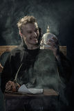 Halloween. Laughing monk with a skull in his hand. Stock Image