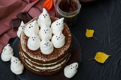 Halloween layer chocolate cake with white chocolate cream and meringue ghosts on top.