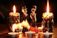 Halloween: le cifre di due scheletri dell'uomo e della donna contro lo sfondo delle candele di combustione nella forma fotografia stock
