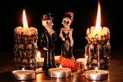 Halloween: le cifre di due scheletri dell'uomo e della donna contro lo sfondo delle candele di combustione nella forma immagini stock libere da diritti