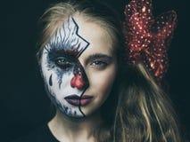 Halloween, le visage d'une fille est une poupée, le plancher d'un visage est mort Une femme avec un maquillage horrible photo stock