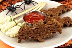 Halloween-Lebensmittel mit Schlägerbroten und käsigen Hexenbesen stockfotografie