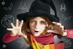 Halloween little girl looking at camera with her hand in frightening gesture stock photography