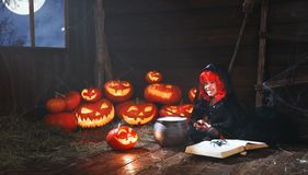 Halloween. little witch child cooking potion   with pumpkin and Stock Photography