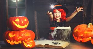 Halloween. little witch child cooking potion   with pumpkin and Royalty Free Stock Photography