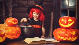 Halloween.  little  witch   conjures with  book of spells,  magi Stock Photos