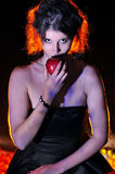 Halloween looking witch in a dark with apple. Orange backlight Royalty Free Stock Image