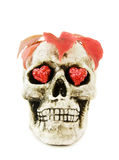 Halloween love with scary skull. Celebrating Halloween with scary human skull decorated with red hearts and dead leaves. Isolated on white background Stock Image