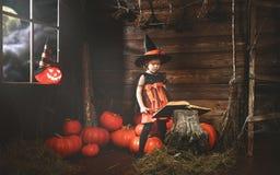 halloween mała czarownica czaruje z książką czary, magi Obrazy Royalty Free