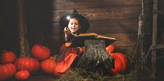 halloween mała czarownica czaruje z książką czary, magi Obraz Royalty Free