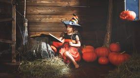 halloween mała czarownica czaruje z książką czary, magi Obrazy Stock