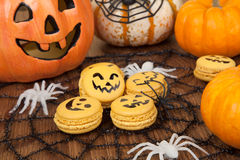 Halloween Macaroons. Closeup of Halloween decor with French pumpkin macaroons and assorted pumpkins Stock Image