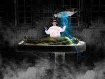 Halloween Mad Scientist Frankenstein Monster. A Halloween scene or horror. A Mad scientist brings to life a Frankenstein monster in his evil lab or laboratory Royalty Free Stock Images