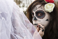 Halloween make-up. Woman makes a Halloween make-up wearing Day of the Dead Royalty Free Stock Photo