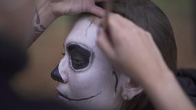 Halloween. Make-up artist applies make-up to girl face. Makeup artist applies make-up to girl face. Halloween holiday stock video