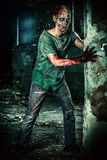 Halloween make-up. Horrible scary zombie man on the ruins of an old house. Horror. Halloween Stock Photo
