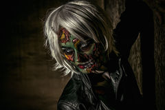 Halloween make-up. Terrible bloodthirsty zombie woman in the slums. Body-painting project. Glamorous zombie girl. Halloween make-up. Horror Stock Image