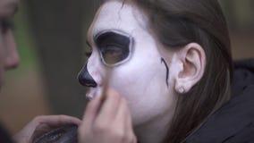 Halloween. Makeup artist applies make-up to female face. Makeup artist applies make-up to girl face. Halloween holiday stock footage