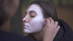 Halloween. Makeup artist applies make-up to girl face. Makeup artist applies make-up to girl face. Halloween holiday stock footage