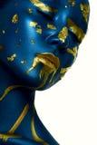 Halloween Makeup. Closeup beauty young Woman with blue gold Skin Stock Photo