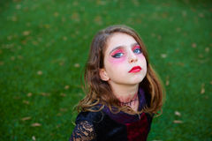 Halloween makeup kid girl blue eyes in outdoor lawn Stock Images