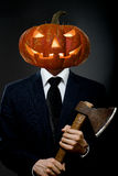 Halloween. Man in black costume with pumpkin head  with axe, Halloween concept Stock Photo