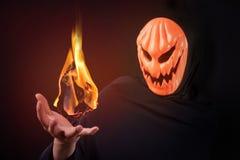 Halloween man with pumpkin mask control fireball. Mystery man with orange pumpkin evil mask control magic fireball on his hand, Halloween night costume concept stock images